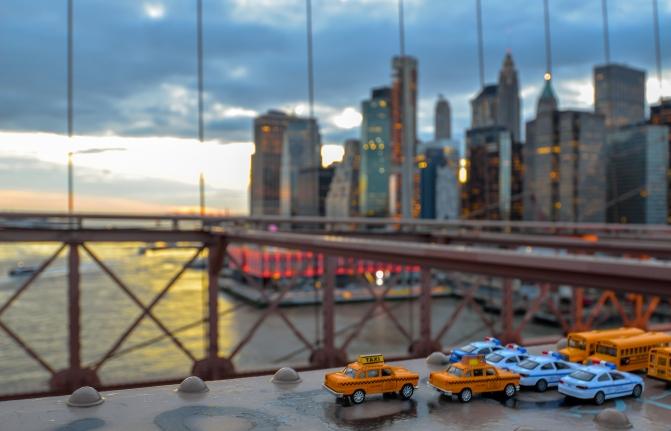 Small car toys on the bridge leading into Manhattan
